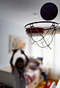 Boy throwing ball into hoop at children's room - MGOF001763