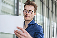 Portrait of young businessman with  digital tablet in front of an office building - DIGF000313