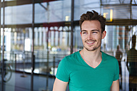Portrait of smiling young man with stubble standing in front of glass facade - DIGF000322