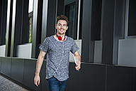 Portrait of walking young man with headphones and digital tablet - DIGF000328