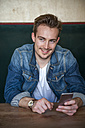 Portrait of happy young man sitting in a coffee shop - DIGF000346