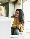 Two smiling women talking in office - UUF007080