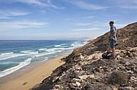 Spain, Canary Islands, Fuerteventura, North coast, beach of Barlovento, hiker - WWF003952