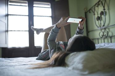 Woman lying in bed using smartphone - GEMF000868