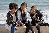 Three young women sitting on wall looking at smart phone - MAUF000452
