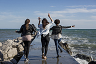 Three young women having fun on breakwater at the sea - MAUF000455