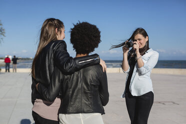 Young woman with camera photographing friends - MAUF000461
