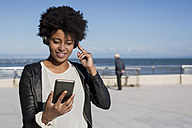Young woman listening music with smart phone - MAUF000467