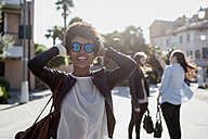 Young woman with sunglasses in the city with her friends - MAUF000473
