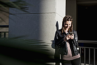 Young woman leaning on wall using smart phone - MAUF000479