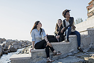 Three young women sitting on wall by the sea - MAUF000482