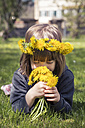 Little girl with floral wreath lying on meadow smelling dandelions - LVF004779