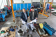 Two engineers with construction plan in front of hydraulic cylinder - DIGF000357