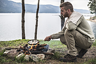 Bulgaria, man frying rudd at camp fire at shore of Dospat Reservoir - DEGF000785