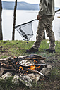 Bulgaria, man frying rudd at camp fire at shore of Dospat Reservoir - DEGF000791