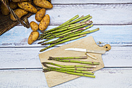 Green asparagus and pocket knife on wooden board - LVF004800