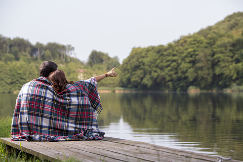 Back view of young couple sitting on a jetty at lake - ZOCF000054