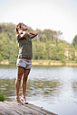 Young woman stretching on a jetty at lake in the morning - ZOCF000057