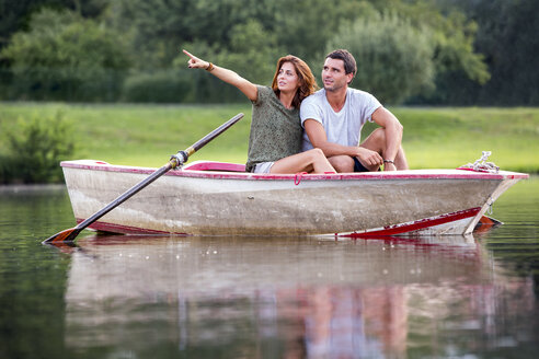 Young couple sitting in a rowing boat on lake looking at distance - ZOCF000063