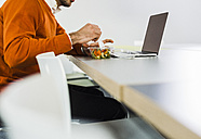 Young man having a salad at desk in office - UUF007101