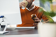 Young man having a snack at desk in office - UUF007104