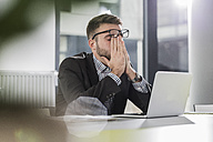 Exhausted young man with laptop in office - UUF007110