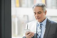 Senior businessman looking on cell phone - UUF007128