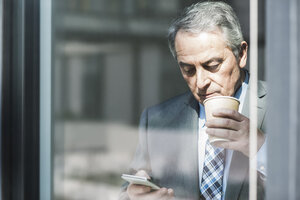 Senior businessman holding coffee to go looking on cell phone - UUF007131