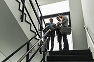 Three businessmen with digital tablet and cell phone in staircase - UUF007143