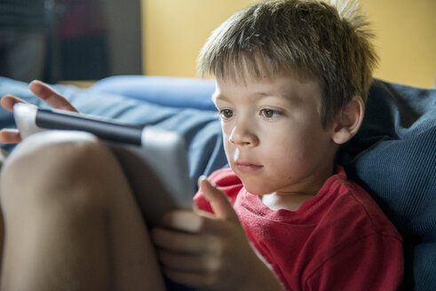 Young boy using digital tablet at home - ZOCF000072