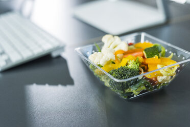 Plastic bowl with vegetables on desk in office - UUF007222