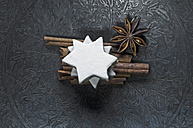 Cinnamon stars, cinnamon sticks and star anise on metal plate - ASF005888
