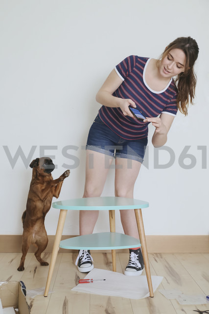 Woman taking a photo of her finished flatpack furniture - RTBF000153