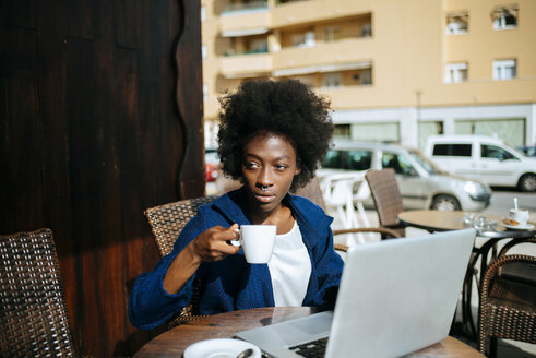 Young woman with laptop sitting in a street cafe drinking coffee - KIJF000329