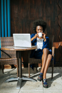 Young woman with laptop sitting in a street cafe drinking coffee - KIJF000332