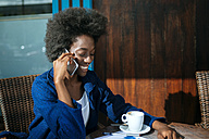 Portrait of young woman talking on mobile phone while drinking coffee in a street cafe - KIJF000338