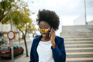 Portrait of young woman wearing mirrored sunglasses talking on mobile phone - KIJF000344