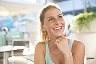 Portrait of happy young woman at outdoor cafe in summer - ZOCF000076