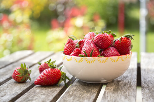Bowl of strawberries on wooden garden table - SARF002704