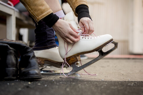 Close-up of woman putting on ice skates - ZOCF000079