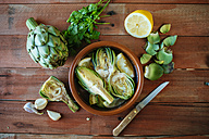 Clay pot with sliced artichokes in water with lemon - KIJF000362