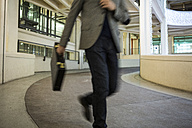 Businessman running on driveway of builing in a hurry - ZOC000091