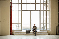Hipster businessman with briefcase waiting in front of door in industrial building - ZOCF000094