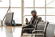 Portrait of young businessman wearing beany hat using smart phone - ZOCF000097
