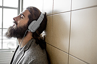 Young bearded man listening music with headphones - ZOCF000100