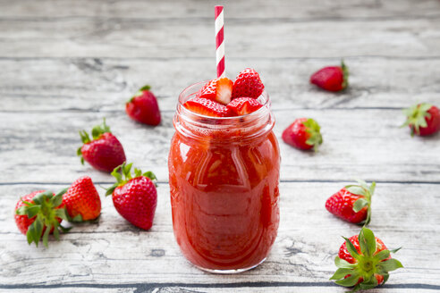 Glass of strawberry smoothie and strawberries on wood - LVF004813