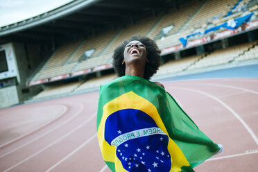 Young black athlete in stadium carrying Brazilian flag - KIJF000379
