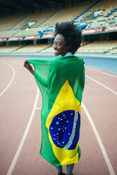 Young black athlete in stadium carrying Brazilian flag - KIJF000382