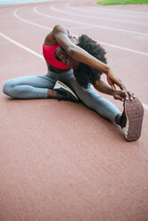 Young black athlete stretching before race in stadium - KIJF000385
