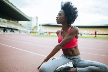 Young black athlete stretching before race in stadium - KIJF000388